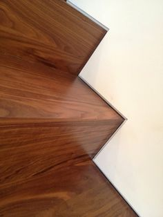 "Custom walnut stairs with the use of a Fry drywall reglet, providing a 1/2"" reveal consistent to each tread and riser 