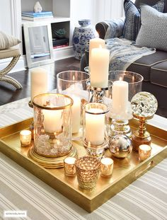 Make a visual statement with a clustered grouping of metal and glass candleholders in varying heights on your coffee table. Coffee Table Centerpieces, Coffee Table Tray, Coffee Table Styling, Decorating Coffee Tables, Coffee Table Candle Decor, Candle Tray, Coffee Candle, Tray Decor, Decoration Table