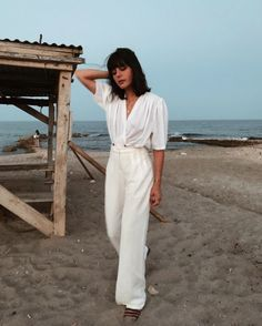 the evening beach strolls in a white summer playsuit.