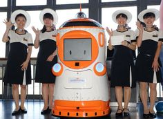 Staff pose next to the newly introduced guide robot, Tawabo, at the Tokyo Tower's observation floor. The 1.6m tall robot provides spoken information in English, Chinese, Korean and Japanese and a digital information display.