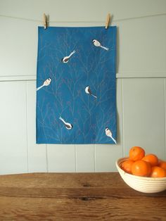 """This is a tea towel with my textile design """"Berry Branch"""" in Persian  Blue/Red, with chickadees among branches of red berries.  Our fabric is digitally printed (in the US) on a linen/cotton blend  (55%linen / 45%cotton). Once printed, the towels are cut and sewn, here in  the studio. Each towel has a hook for hanging top/center on the back of the  design, and is hemmed on all four sides.  Approximate size is 16 by 25 inches.  Hand-washing recommended to preserve the colors, Machine-wash safe…"""