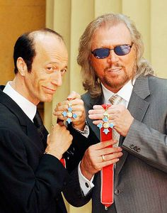 The two surviving members of the Bee Gees Robin and Barry Gibb hold their CBE's after receiving them from the Prince of Wales on May 27 2004 at...
