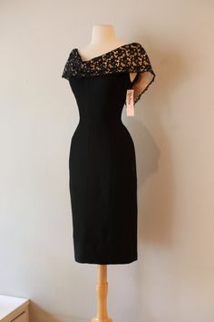 Absolutely divine 1950s cocktail dress. Ultra fitted and shape enhancing. Dress features a wide off the shoulder satin collar with black lace overlay, princess seams and side pockets. The fabric feels like a wool silk blend. Original metal zipper up the back. MEASUREMENTS: Bust: 37 Waist: 30 Hips: 40 Shoulder seam to hem: 41 Excellent vintage condition, clean and ready to wear. *Please compare measurements to a garment you currently own to ensure proper fit! visit the shop…