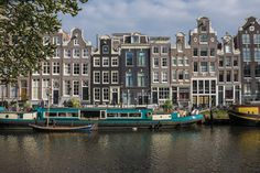 Canal Houses and blue houseboat on Amsterdam Singel - near Blauwburgwal canal.