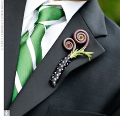 A polka-dot ribbon wrap matched the lighthearted feel of the fiddlehead ferns in the groomsman bouts. Their green-and-white ties coordinated with the bridesmaid dresses.