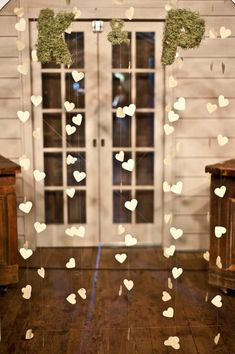 A mossy backdrop can include your wedding initials at your ceremony. I love the hanging hearts, too.