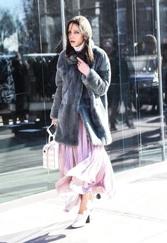 A fur jacket layered over a pink flowing dress.
