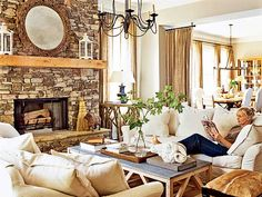 Warmth in this living room comes from the mix of textures, from the burlap curtains to the white linen slipcovers and the hide stool to the rough-hewn mantel on the local-stone fireplace. (Photo: Dominique Vorillon)