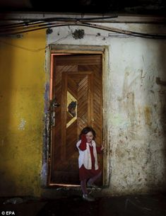 A little girl stands in an apartment block on Horea Street in a slum