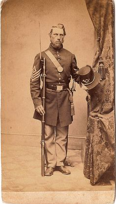 Asa W. Hebbard wearing a frock coat with 1st sgt. chevrons and holding a model 1855 Hardee Hat with infantry bugle. This is a good example of the dress uniform of Union Infantry.