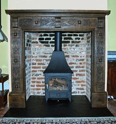 Bespoke, locally sourced hand carved oak mantel with original Tudor brick chamber and slate tiled hearth fitted in the old Lord Mayor of London's country retreat Langdon hills, Essex by Scarlett Fireplaces 2009