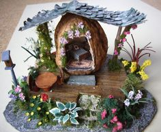 Tiny homes for fairies, in walnut shells, with beautiful surrounding gardens.  These two little walnut shell fairy houses were made by Ann, a dolls housing friend with incredible skill at making miniature flowers.  Each tiny house is a real walnut shell, carefully cut (they break more often than not!) and inside a tiny home has been created, surrounded by an atmospheric garden.  One has a corrugated tin roof, the other a tiled. One has a bedroom scene, the other a comfy living room complete…
