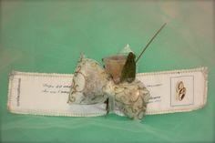 """SEGNALIBRO - Realizzato in tessuto e cotone. Sul cotone è possibile stampare frasi personalizzabili. Arricchito con fiori realizzati in organza. I confetti si inseriscono nel """"fiocco"""" di telina di tnt."""