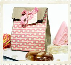 Trim top of lunch bag with decorative scissors, cover the front with patterned paper, put the gift in the bag, fold the top down, punch two holes, thread ribbon through holes and tie in a bow, add gift tag. Quick, cute, and easy wrapping for any occasion!