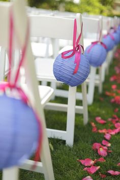 Chinese paper lanterns tied with ribbon as pew / chair wedding decorations.