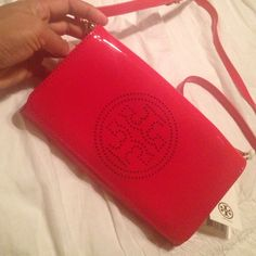 Beautiful Authentic Tory Burch Clutch Brand new with tags! Authentic Tory Burch clutch/crossbody red patent leather. Has removable straps so you can use a a clutch. The only imperfections are little indentations from being squished in my closet. I guess that's what dust covers are for too . I tried taking better pictures but it's so small that it doesn't show. Other than that, the bag is in perfect condition. Please no trades and I won't respond to low ball offers. Smoke free/pet free home…