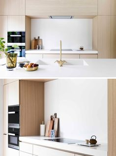 In this modern kitchen with light wood cabinets and white countertops, an integrated stove top sits flush with the counter and built-in dual ovens give the kitchen a more streamlined look.
