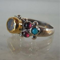 This is a unique and one off engagement ring. At the center, you will find a genuine rainbow moonstone in 24K solid gold bezel. The solid gold is also hammered around the moonstone gemstone and makes this ring a true and delightful organic piece. The band is made of sterling silver and a beautiful setting of turquoise and garnet gemstone. This ring can be worn as an engagement ring or just for you to feel special. Measurements: Center stone: 6 mm/8 mm Height above finger - center sto...