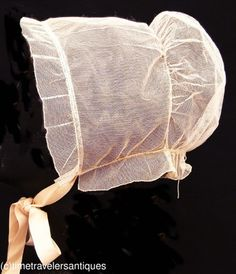 "An original circa 1850 lady's silk tulle cap made to be worn beneath a bonnet. A fine drawstring back and a pretty pleated ruffled edge, with silk satin chin ties that may be later replacements. 8"" deep and 9"" across the face as shown. In very good clean supple as found condition, with only some minor perspiration color at the bottom edge. A rare mid 19th century bonnet accessory."