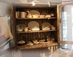Love the weathered cabinet and the white dishes as always