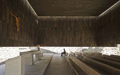 Structured Light: Interior of the Chapel of Retreat by Christián Undurraga (Undurraga Devés Architects). With structural loads carried to the perimeter of the subterranean landscape void, the wood cladding and structural glass walls of the chapel appear to float within a volume of light. The hidden structure enhances a sense of mystery and timelessness. Image © Sergio Pirrone