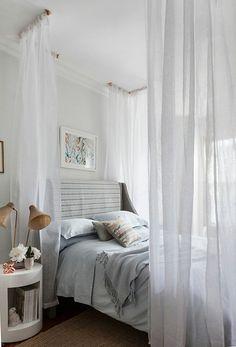 un joli lit dans la suite parentale, murs blancs, lit avec baldaquin, table de chevet en bois