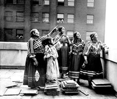 Four Blackfoot women and a girl, wearing traditional regalia, standing on the roof of a building in Chicago, Illinois. People are visible standing and watching in windows of a building in the background. Photographed: 1929. - Photographs from the Chicago Daily News, 1902-1933.