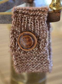 Knitted bracelet with brown iridescent yarn and a button for clasp