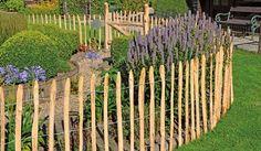 Staketenzaun aus Kastanienstaketen als dekoratives Element in einem Bauerngarten