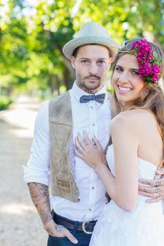 boho bride with flowers in hair and groom in straw hat and leather vest