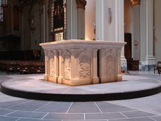 The altar at St. James Cathedral, Seattle, WA is of white marble and dates from 1994.  On the west side, two panels from the original high altar of the Cathedral, 1907, feature imagery of wheat and grapes, symbols of the Eucharist.  This same imagery is echoed on the other three sides, with panels by three contemporary artists:  Mary Jo Anderson (south), Randall Rosenthal (east), and Larry Ahvakana (north).