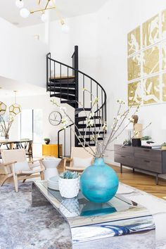 Living room with a large art, a mirrored coffee table, and stainless steel staircase