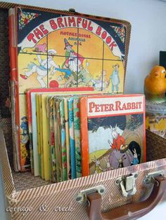 A vintage child's suitcase holds a selection of colorful vintage children's books, adding instant charm to our vintage-inspired baby shower decor.