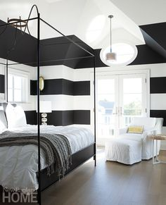 Bold stripes contrast with the pencil-thin lines of the wrought-iron bed to create visual interest in this guest room.  Architecture: Brian Goodridge, Thor Studios Interior design: John Stefanon, JFS Design Studio Modern Movement | New England Home Magazine