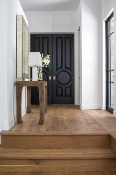 Modern Farmhouse Inspiration: Foyer with black and white mirror mounted above a wood chinosiserie console table topped with a white table lamp and placed on rustic wood floors that lead to black circle paneled double front doors finished with gold knobs. Black Front Doors, Double Front Doors, Asian Front Doors, The Doors, Wood Doors, Painted Doors, Sliding Doors, Black Interior Doors, Interior And Exterior