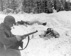 A GI belonging to the 83rd Infantry Division reloads his M1 rifle in the section of the front near the Belgian town of Houffalize, Jan 15, 1945. Two German KIAs testify to the bitter fighting that continues.