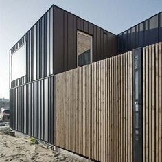 This zinc-clad building comprises two separate dwellings for a mother and son, each with its own patio.