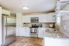 Renovated kitchen by Dwelling Studio with white painted cabinets, granite counters. stainless steel appliances, herringbone faux wood tile flooring, open shelves, subway tile backsplash
