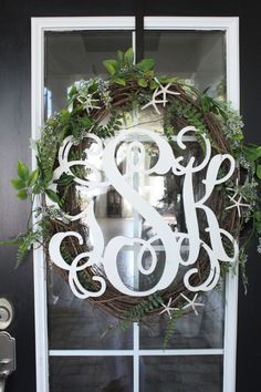A beautiful monogrammed wreath with starfish and ferns. Coastal outdoor decor for any home | Starfish Cottage