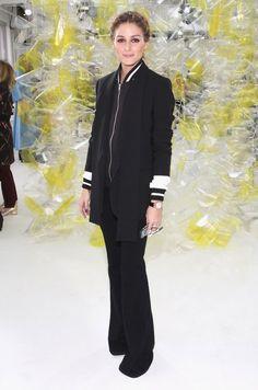 Olivia Palermo com look todo preto com calça flare de alfaiataria.