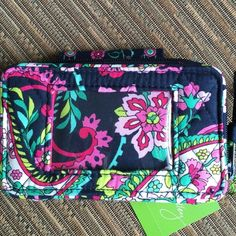 """Vera Bradley Smart Phone Wristlet Petal Paisley Vera Bradley Smart Phone Wristlet NWT~Petal Paisley~ • Larger all-in-one phone case and wallet • Zip-around compartment reveals three card slips, a bill compartment, a coin purse and an outer ID window. • Fits an iPhone 5/5s in an OtterBox Case • Wallet strap I clips to wrap it around a handbag or tote handle. • The snap flap on the phone compartment is secure, yet easy to access. Size: 5 1/2"""" W x 3 1/4"""" H x 2"""" D with 6"""" wrist strap~SMOKE FREE…"""