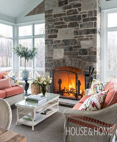 A stone fireplace keeps the screened-in porch warm during late fall and early spring. | Photographer: André Rider | Designer: Scott Yetman