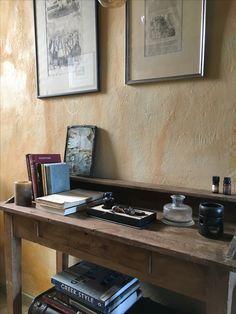 Ενα παλιό  secretaire του παππού στέκει στην είσοδο του σπιτιού με τακτοποιημένα πάνω του και γύρω του όμορφα βιβλία, μελανοδοχείο και γκραβούρες και ένα λύχνο για αιθέρια έλαια.