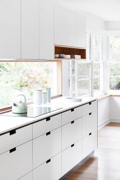 Why You Should Choose Drawers Over Cabinets in Your Kitchen -Banks of drawers (and a breathtaking backsplash window) in a kitchen