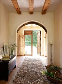 I love everything about this, the arch, the exposed beams, the pebbled floor, the front door, everything.