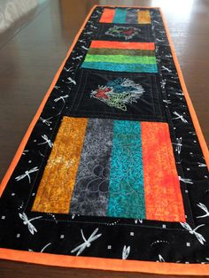 Bright blocks of orange and green and gold interspersed with Sashiko style embroiderd butterflies and dragonflies surrounded by a border of black