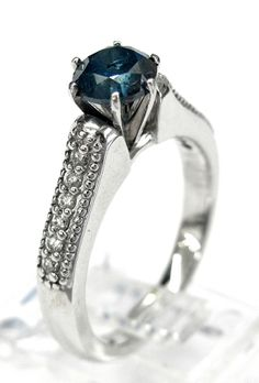 Ladies 14kt white gold diamond ring. Ring is set with 1 brilliant round cut color treated blue diamond weighing 1.13ct and 12 brilliant round cut white diamonds weighing .33ct. A total of approximately 1.46ct.