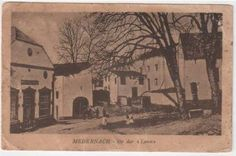 "old postcard from Medernach, left hand side milk-dairy building and right a stone cross that has now been moved further down this place called ""op der Lann"" because of the lime tree you still see on the picture (Lann is Luxembourgish for lime tree) / in Medernach op der Lann (bij de lindenboom die je rechts in beeld ziet), met een oud wegkruis (staat nu verder naar beneden) en links de zuivelfabriek van toen."