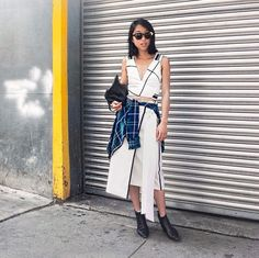 How to Wear an Envelope Midi Skirt - Shine by Three blogger wearing a black and white envelope midi skirt, matching crop top, + plaid shirt wrapped around the waist and sleek black ankle boots. Major outfit inspiration.