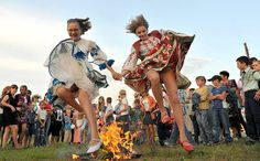 Kupala Girls  Belarusian girls in traditional costumes jump the fire on Ivan Kupala Night, a Slavic holiday originating in pagan times. (Turov, Belarus.) Photo: Viktor Drachev / AFP / Getty Images
